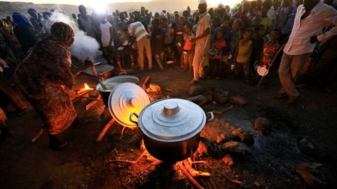 Ethiopian refugees fleeing from the ongoing fighting in Tigray region, wait for food at the Um-Rakoba camp, on the Sudan-Ethiopia border, in the Al-Qadarif state