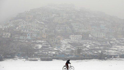 An Afghan man rides a bicycle during snowfall in Kabul