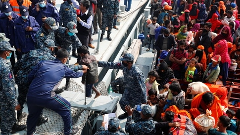 Bangladesh Navy personnel help a disabled Rohingya refugee child to get off from a navy vessel as they arrive at the Bhasan Char island in Noakhali district