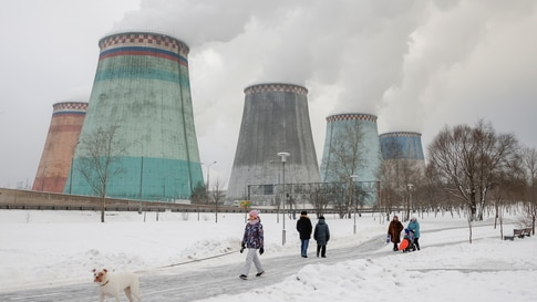 People walk in a park near chimneys of a heating power plant on a cold winter day in Moscow