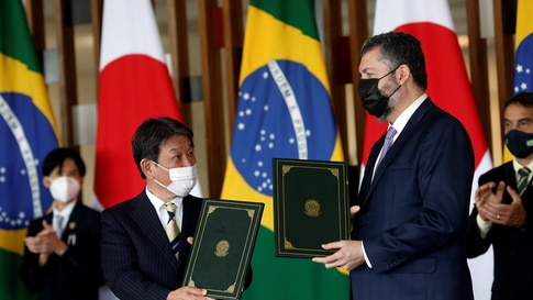Japan's Foreign Minister Toshimitsu Motegi and his Brazilian counterpart Ernesto Araujo pose after signing a bilateral agreement during a ceremony in Brasilia