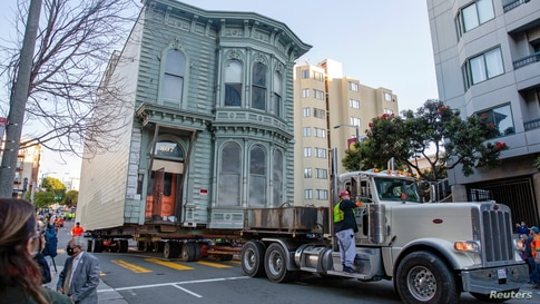 Workers prepare to move a 139-year-old Victorian house to a new location in San Francisco
