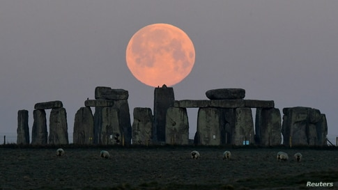 """The full moon, known as the """"Super Pink Moon"""", sets behind Stonehenge stone circle near Amesbury"""