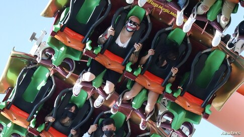 People ride a roller coaster at Six Flags Magic Mountain amusement park on the first day of opening, as the coronavirus disease (COVID-19) continues, in Valencia