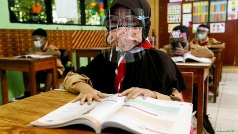 Elementary school students wearing face masks and face shields attend class, as schools reopen amid the coronavirus disease (COVID-19) pandemic, in Jakarta