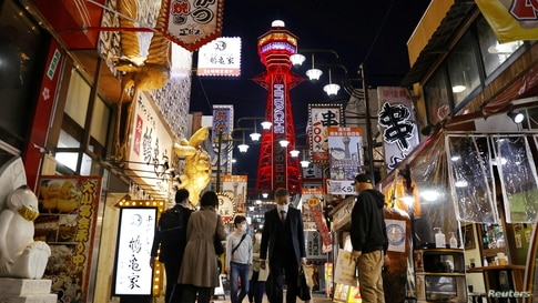 Pedestrians are seen in front of the Tsutenkaku Tower in Osaka