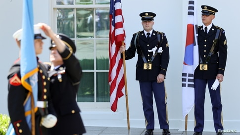 Military honor guard members with U.S. and Korean flags prepare for the arrival of South Korea's President Moon to meet with U.S. President Biden at the White House in Washington