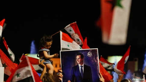 Supporters of Syria's President Bashar al-Assad celebrate before the results of the presidential election in Damascus