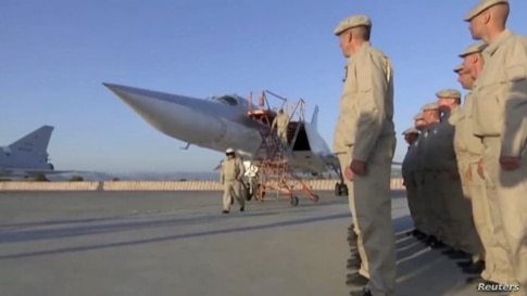 A still image taken from video footage shows Russian service members after the landing of a Tupolev Tu-22M3 long-range bomber landing at the Hmeymim base