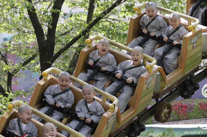 Shaven-headed children ride a roller coaster during their visit at the Everland amusement park in Yongin, South Korea, Thursday, May 2, 2019.