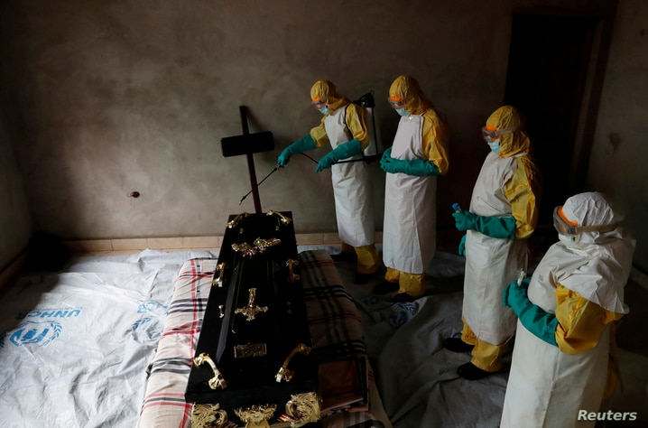 A healthcare worker sprays a room during a funeral of Kavugho Cindi Dorcas who is suspected of dying of Ebola, in Beni, North Kivu Province of Democratic Republic of Congo, Dec. 9, 2018.