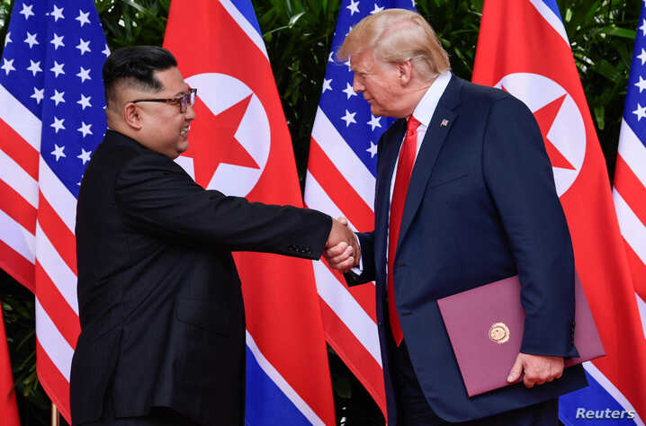 U.S. President Donald Trump and North Korea's leader Kim Jong Un shake hands during the signing of a document after their summit at the Capella Hotel on Sentosa island in Singapore, June 12, 2018.