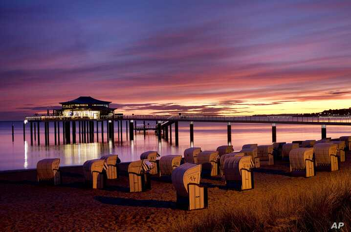 The sun is about to rise behind a sea bridge with a restaurant at the Baltic Sea in Timmendorfer Strand, Germany, early Monday, Oct. 8, 2018. (AP Photo/Michael Probst)