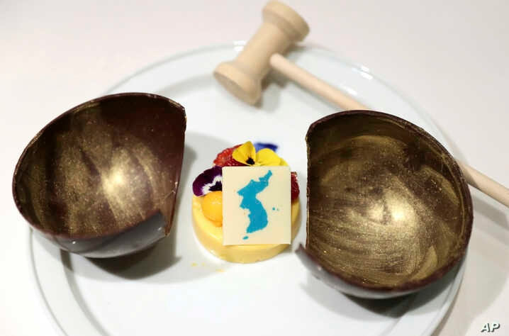 This undated photo provided by South Korea Presidential Blue House Tuesday, April 24, 2018, shows mango mousse decorated by a blue flag symbolizing a unified Korean Peninsula. The item is on the menu for a planned banquet after the April 27 summit between