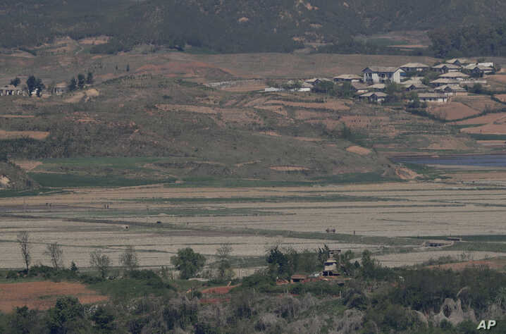 North Korea's Kaepoong town is seen behind a North Korean military guard post, bottom, from the unification observatory in Paju, South Korea, May 6, 2019.  North Korea says it is suffering its worst drought in decades amid concern of a food crisis..