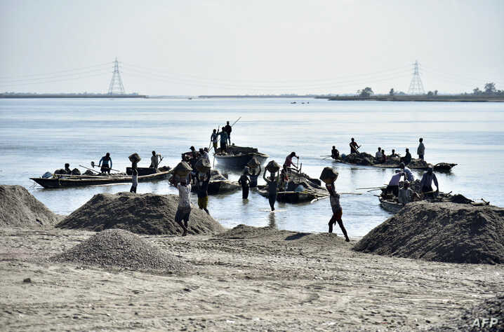 Laborers extract sand from the riverbed of the Beki River in the district of Barpeta of the northern Indian state of Assam on November 4, 2019.