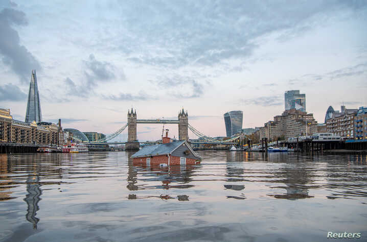 A mock-up of a typical British suburban home is seen sinking into the River Thames, in a protest by Extinction Rebellion to demand faster government action on climate change in London, Britain November 10, 2019.