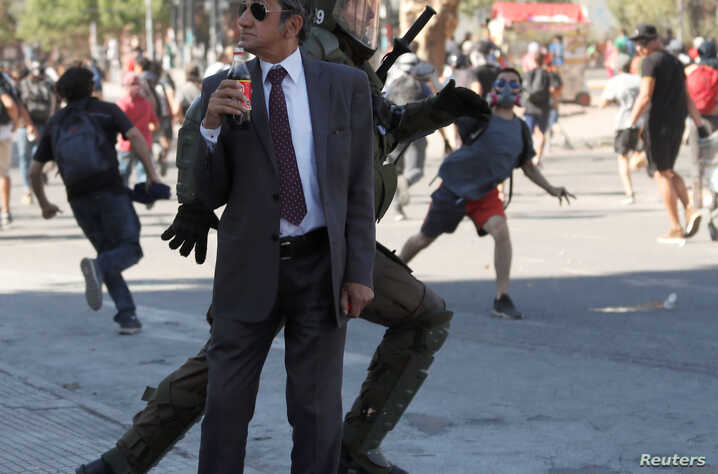 A man drinks a Frucola as a policeman chases demonstrators during a protest against Chile's government in Santiago, Chile December 4, 2019.