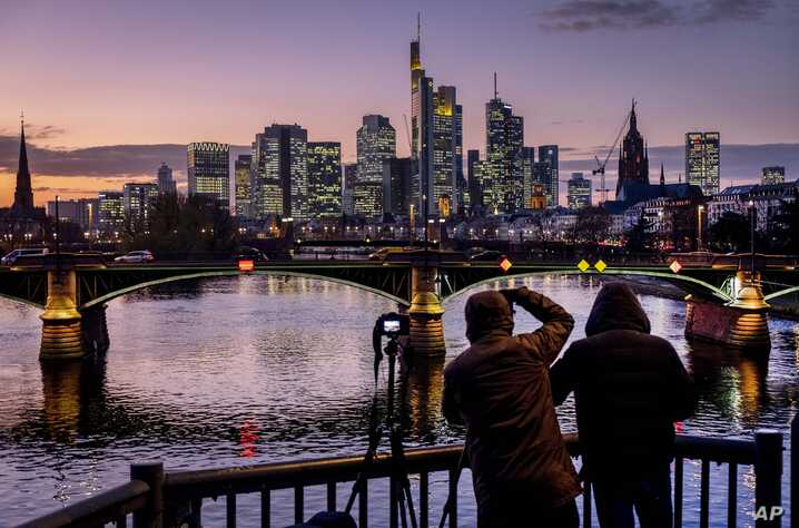 Two men take photographs of the buildings of the banking district in Frankfurt, Germany, after sunset.