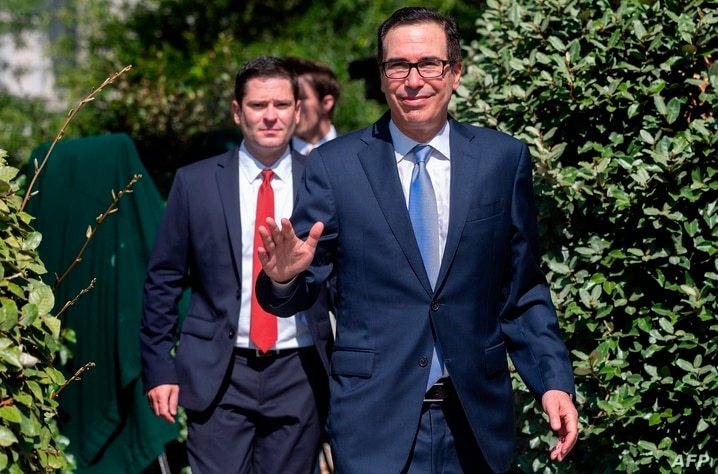 US Treasury Secretary Steven Mnuchin waves as he departs a television news interview at the White House on July 9, 2020, in…
