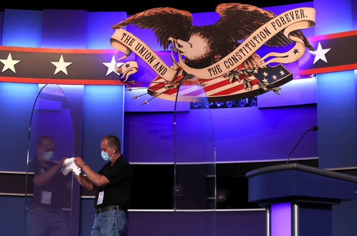 NASHVILLE, TENNESSEE - OCTOBER 21: A worker claens newly installed plexiglass shields on the debate stage inside the Curb Event…