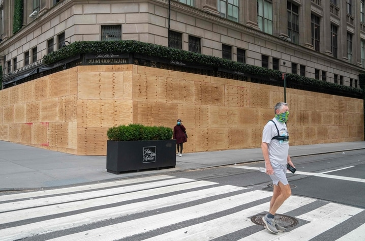 NEW YORK, NY - NOVEMBER 1: A person walks by a boarded up Saks Fifth Avenue on November 1, 2020 in New York City. Businesses…