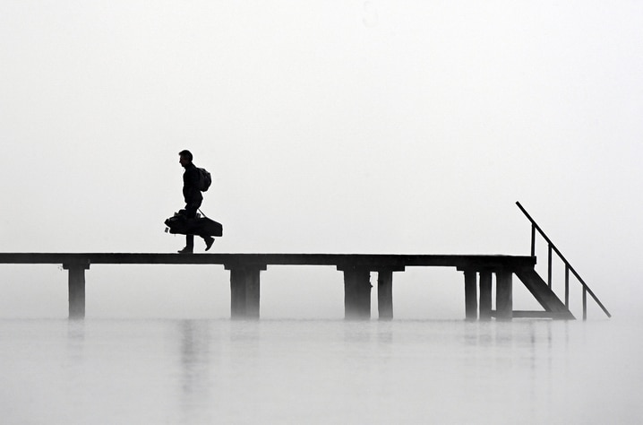 A man walks on a pier at lake Ammersee in Stegen, southern Germany, during heavy fog with temperatures around three degrees…
