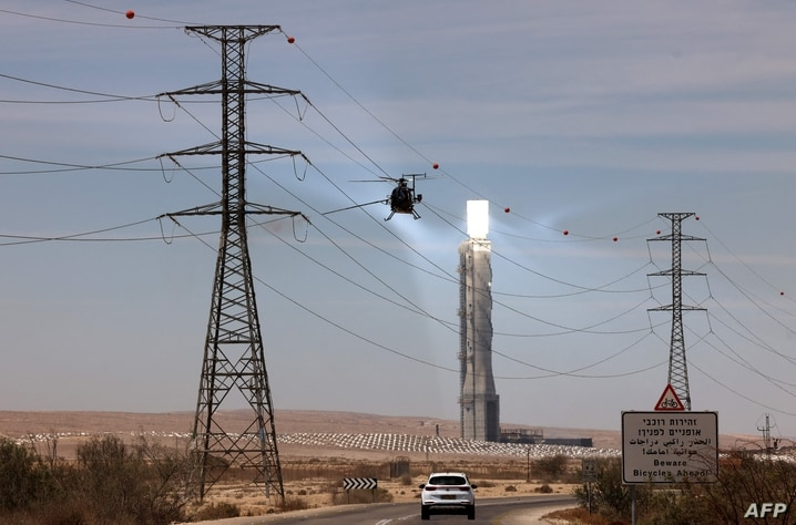 TOPSHOT - A maintenance crew cleans power lines using an helicopter in front of the solar tower of Israel's Ashalim power…