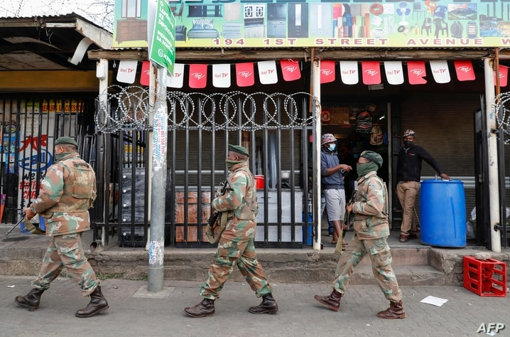 People inside a shop and watch as a member of the South African Defence Force (SANDF) patrols their area in Alexandra township,…