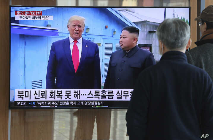 People watch a TV screen showing a file image of North Korean leader Kim Jong Un and U.S. President Donald Trump, left, during…