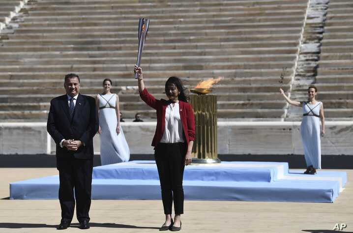 Former Japanese swimmer Imoto Naoko, right, holds the Olympic torch as Hellenic Olympic Committee President Spyros Capralos…