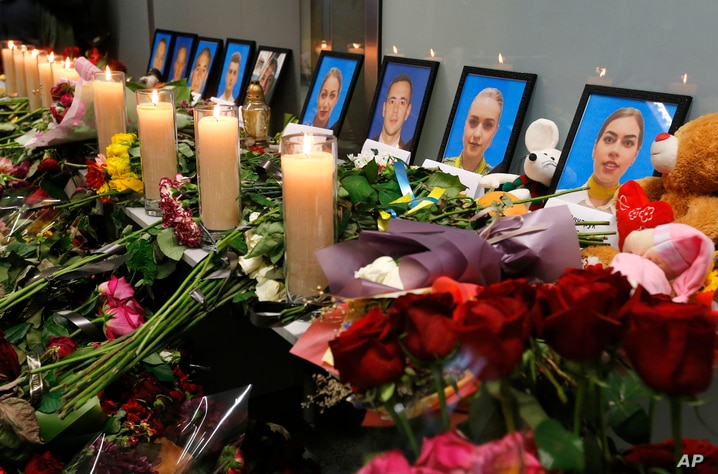 Flowers and candles are placed in front of portraits of the flight crew members of the Ukrainian 737-800 plane that crashed on…