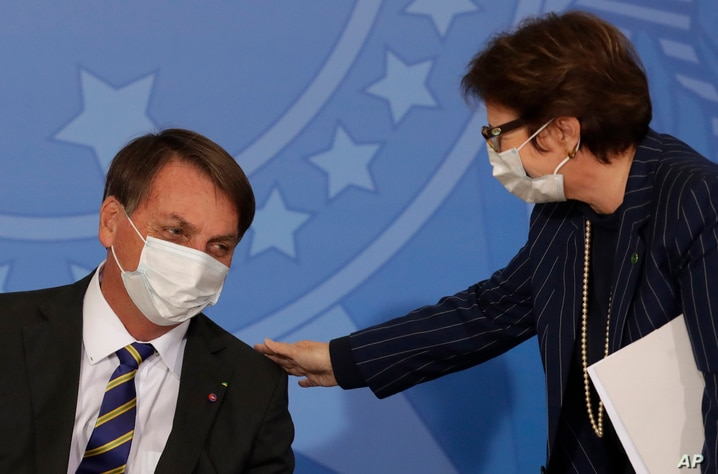 Brazil's President Jair Bolsonaro wearing a protective mask to curb the spread of the new coronavirus, left, talks with…