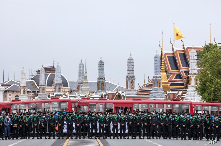 Police officers wearing face masks stand in line, protecting the area surrounding the Grand Palace during during a protest in…