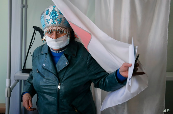 A woman wearing a face mask to protect against coronavirus infection leaves a voting booth at a poling station during Leningrad…