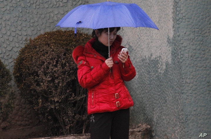 FILE - In this Friday March 16, 2012 file photo, North Korean woman uses a mobile phone on a sidewalk in Pyongyang, North Korea…