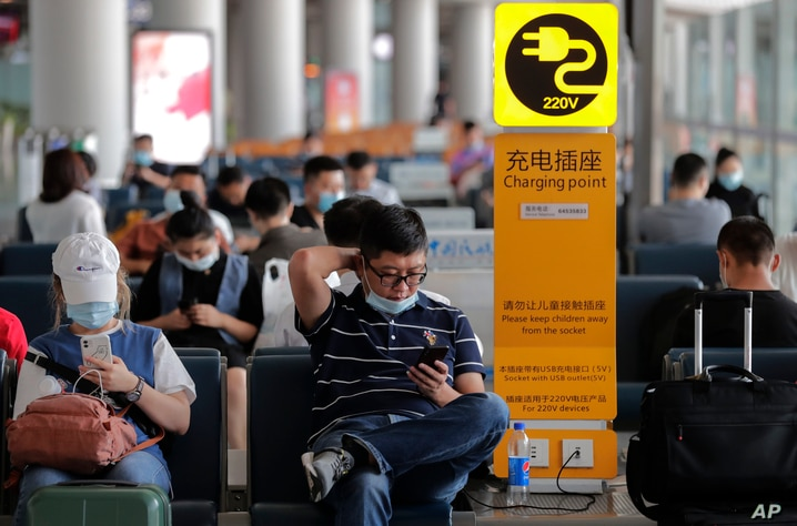 Passengers wearing face masks to help curb the spread of the coronavirus browse their smartphones as they wait for their flight…