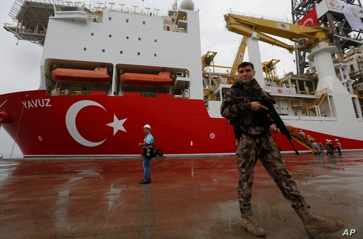 FILE - In this Thursday, June 20, 2019 file photo, a Turkish police officer patrols the dock, backdropped by the drilling ship …