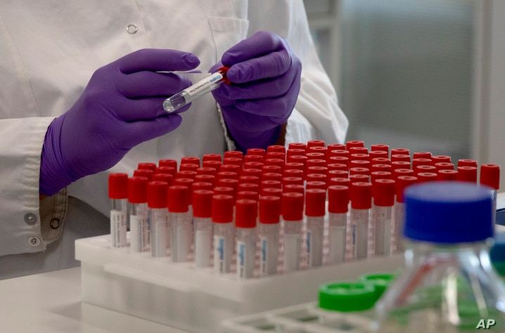 A lab technician looks puts a label on a test tube during research on coronavirus, COVID-19, at Johnson & Johnson subsidiary…
