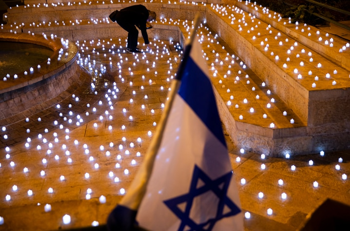 A man turns on LED candles at a memorial for Israel's victims of COVID-19, in Jerusalem, Sunday, Nov. 8, 2020. (AP Photo/Oded…