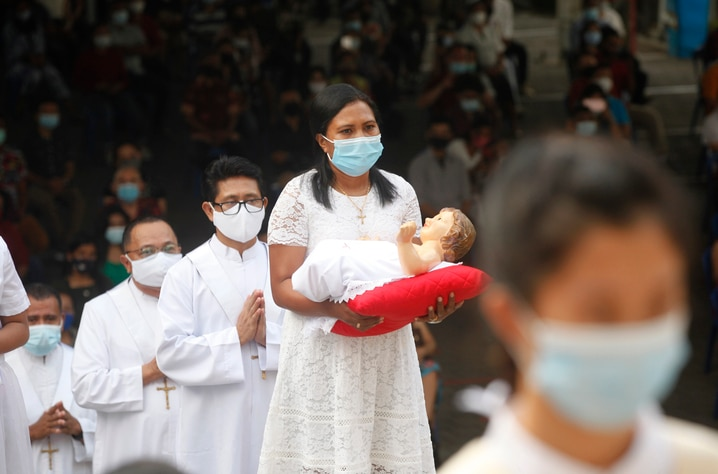 A woman, wearing face mask, carries baby Jesus statue, line up during a procession for a Christmas mass service at a church in…