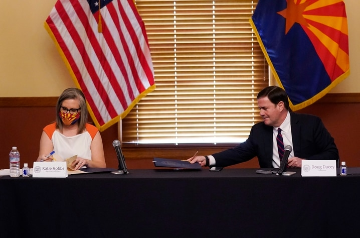 Arizona Secretary of State Katie Hobbs, left, and Arizona Gov. Doug Ducey sign election documents to certify the election…