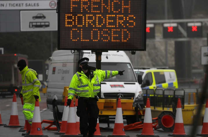A police officer directs traffic at the entrance to the closed ferry terminal in Dover, England, Monday, Dec. 21, 2020, after…