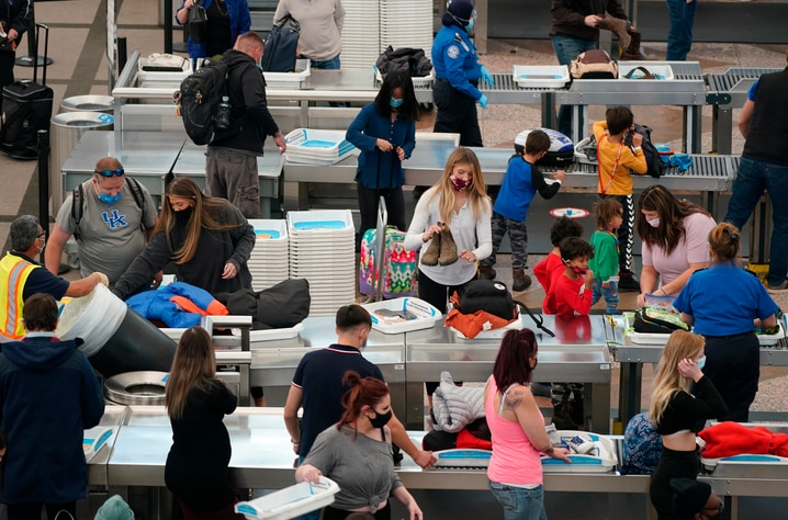 Travelers wear face masks while passing through the south security checkpoint in the main terminal of Denver International…