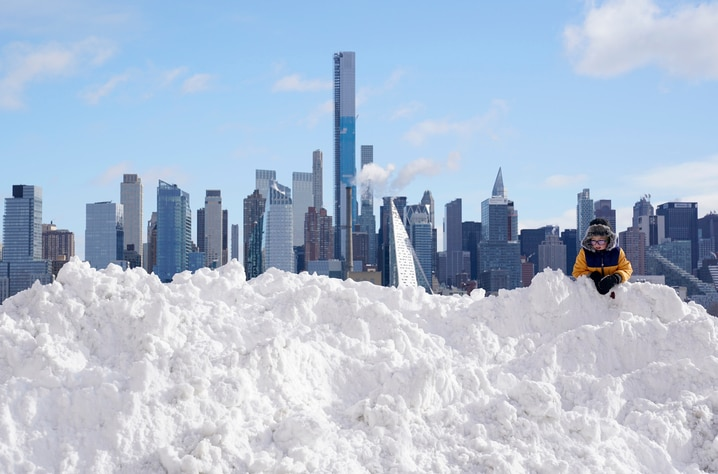 A boy plays on a mound of snow in front of the skyline of New York City in West New York, N.J., Thursday, Dec. 17, 2020. The…