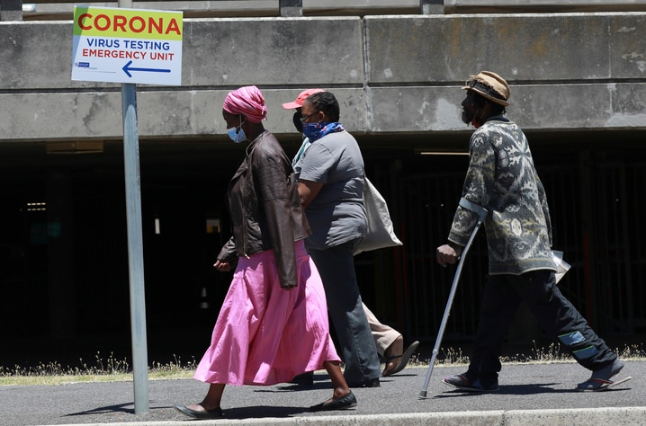 People pass a sign at Groote Schuur Hospital in Cape Town, South Africa, indicating a COVID testing station Tuesday, Dec. 29,…