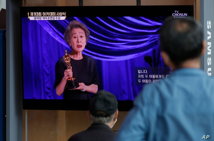 People watch live broadcast of TV showing South Korean actress Yuh-Jung Youn receiving the Oscar for best supporting actress…
