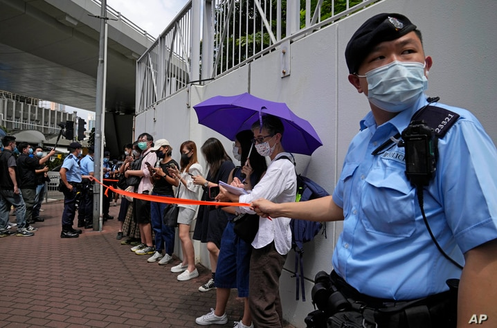 Police get people, including journalists, together to check IDs outside a court in Hong Kong, Saturday, June 19, 2021. A Hong…