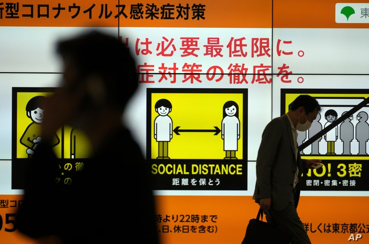 People walk past a public awareness sign for social distancing to help reduce the spread of the coronavirus Tuesday, June 22,…