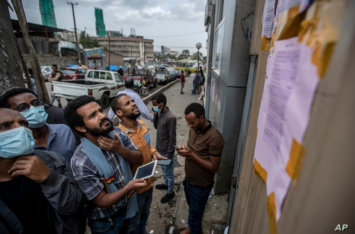 Ethiopians look at electoral results posted on the wall outside a polling station in the capital Addis Ababa, Ethiopia Tuesday,…